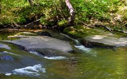 water flowing through  a stream  in willard brook state park,
