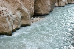 Water flowing through rock formations. Limestone canyon and clear wavy water. Nature background.