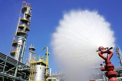 Water flowing vigorously from open fire hydrant as part of the fire extinguishing system testing for safety in the event of an emergency in chemical plants, power plants, oil & gas industry.