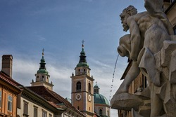 Water flows from a jug in a fountain in Ljubljana, the capital of Slovenia, with a church tower in the background