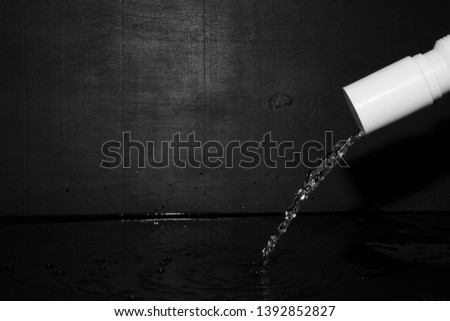 Water flows from the tap. Black wooden background, slow motion. #1392852827