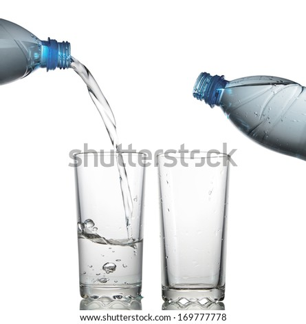 Water flows in a glass from a plastic bottle. isolated on white