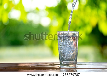 Water flows into a glass placed on a wooden bar.