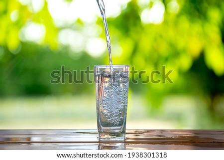 Water flows into a glass placed on a wooden bar. Stock foto ©