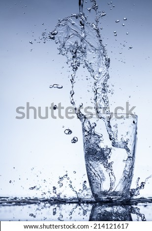 Water flows into the glass with splashes