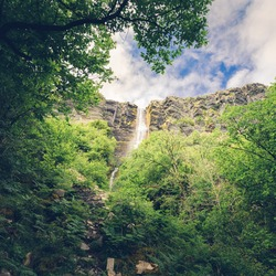 Water flows over the edge of The Devils Chimney,  Irelands tallest waterfall with a height of 150m. Situated in the Mountains at Glencar Lake, Sligo, Ireland