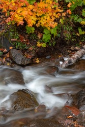 Water flows rapidly down Jacobs Creek near Eagle River Michigan. Autumn colors in the background. Near the popular Jam Pot