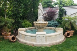 Water fountain (fontana) in a yard, statue of a lady with decoration and ornaments, private property decorated with flower pots, pottery, amphora and green lawn