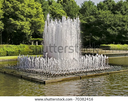 Water fountain in japanese public park in a middle of a pond