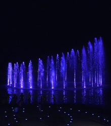 Water fountains on night background in Smart City Malta. Dancing water fountains. Colourful water fountains show