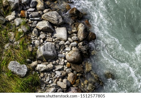 Water from a flowing stream taken from above with large stones #1512577805