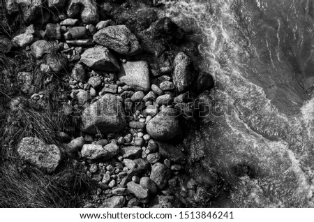 Water from a flowing stream taken from above with large stones #1513846241