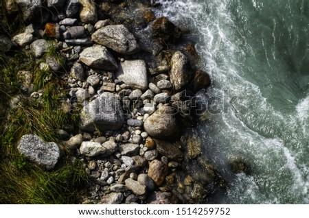Water from a flowing stream taken from above with large stones #1514259752