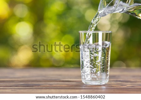 water from jug pouring into glass on wooden table outdoors