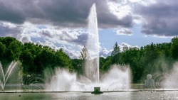 Water from the fountain. Top of high water stream of fountain behind cloudy sky. Fountain in river against dramatic sky.