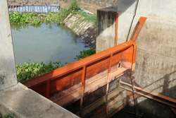 Water gate controls water level supports agriculture in country side of Thailand. Metal sling for pull up - down installed beside concrete wall. Canal background. Water management concept.