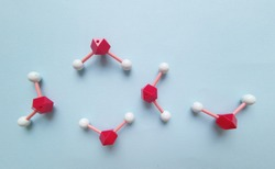 Water (H2O) molecules. Molecular structure model of water molecule (ball-and-stick model). Polar inorganic compound, tasteless and odorless liquid. Red=O, white=H.