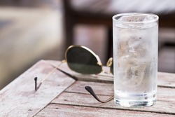 Water in a glass with ice placed on wooden table with glasses for a toast to the health and thirst
