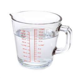 Water in measuring cup isolated on white background