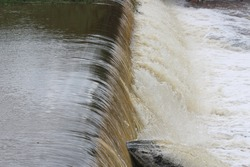 Water in waterfall on the dam wall, running water in free fall in reuse of dam.