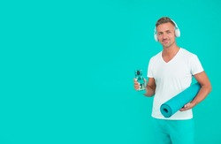 Water intake helps with thirst. Athlete hold water bottle and yoga mat blue background. Thirst and dehydration. Thirst and drinking during exercising. Drink water to avoid thirst, copy space