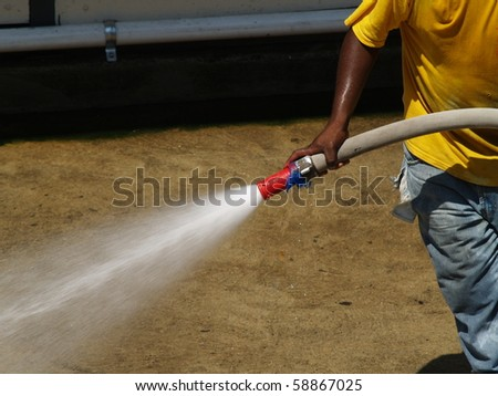 Water is directed from hose being pulled by a laborer.