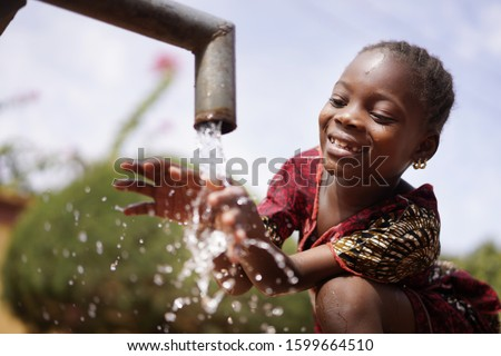 Water is Life for African Children, Little Gorgeous Black Girl Drinking from Tap Foto stock ©