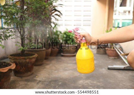 water is sprayed in air by yellow spray bottle #554498551