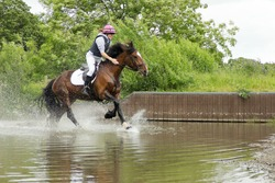 water jump-happy smiley rider and her horse enjoying riding through the water jump at an equestrian event on a summers day