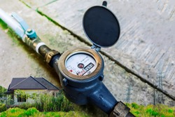 Water meter on concrete with home and green nature background, Measuring device, Open cover of water meter to check counter number of water consumption, water pipe and meter with waterspout of home