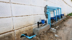 Water meter with plumbing beside the wall. Many devices used to measure water volume on white wall for calculating and displaying customer's water consumption with copy area. Selective focus