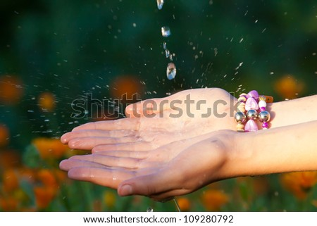 Water on hands on summer day, garden, splashing