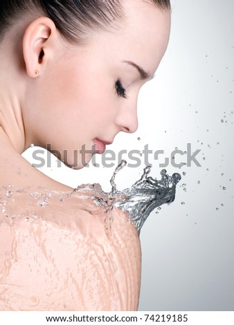 Water on the shoulder of beautiful woman with clean skin - vertical