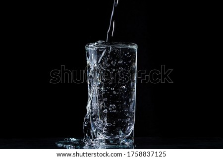 Water overflows the glass. Photo on a black background. Pure and purified water. Water pouring out of a glass Foto stock ©