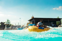 Water park adventure aqua park with cool people having fun on the water slide with friends and familiy in the aqua fun park glides playing happy in the sunlight and water splashes blue sky background