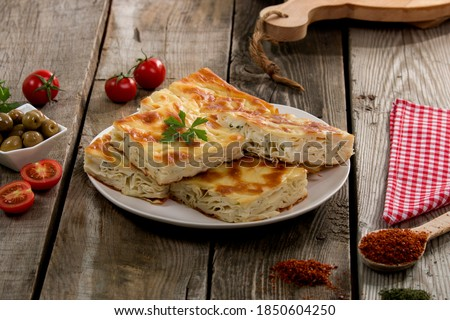 Water pastry on the plate. Composition of water pastry, tomato, hot pepper and olives on old wooden table. Stok fotoğraf ©
