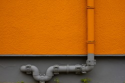 Water pipe and orange wall