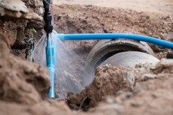 Water pipe break .Exposing a burst water main, focused on the spraying water and the pipe.