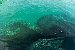 Water pollution caused by oil from fishing boats. Useful for background or texture. This environmental degradation happens when chemical pollutants are discharged into water.