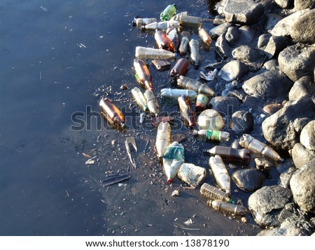 Water pollution - old garbage and oil patches on the surface.