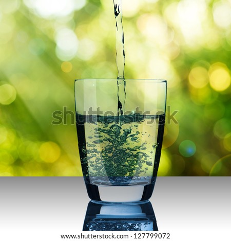 Water pour into glass on summer scene background