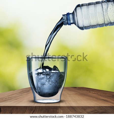 Water pour on to glass with ice cube on wood table