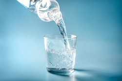 Water pouring from plastic bottle in glass on blue background