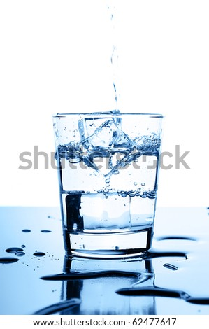 water pouring in to glass with ice cubes on glossy background