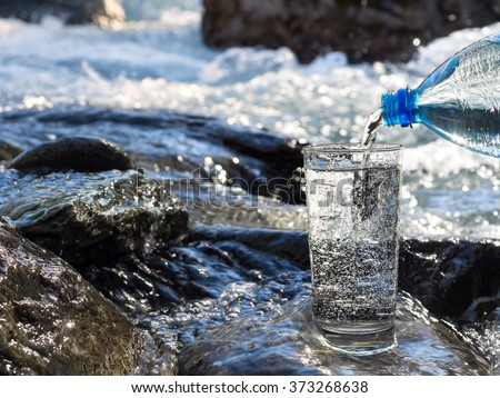 water pouring into a glass from ...