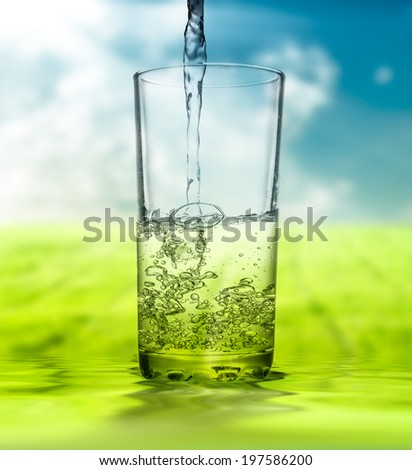 water pouring into glass on  unfocused nature background