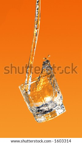 Water pouring into the glass dynamic motion on orange background