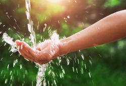 Water pouring splash in hand and nature background with sunshine