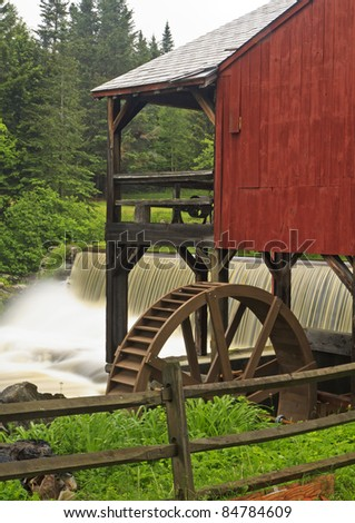 Water pours over a dam next to an old red mill near the Weston Playhouse in Weston, Vermont