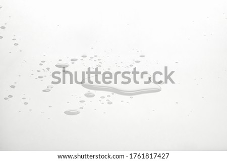 Water puddles and droplets on white reflective surface. Frontal view and deep focus. Foto stock ©